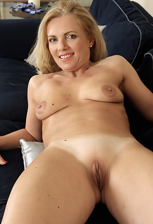 Blonde 47 year old bombshell Britney squatting in front of the couch