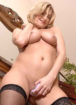 Topless blonde mature lays on the floor and pleasures her pussy with a little toy
