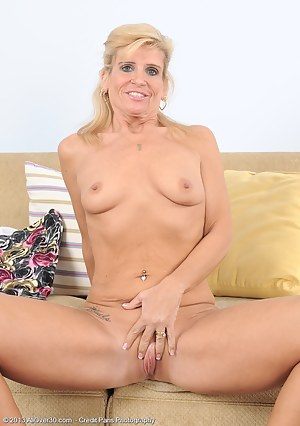 Blonde 49 year old Crystal Jewels spreads wide open on the couch