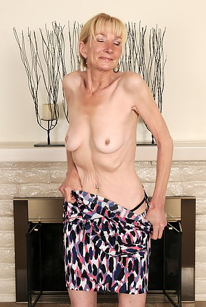 Elegant and blonde 57 year old Pam strutting around the room naked