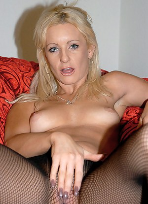 This awesome blonde loves wearing stockings at home. She is laying on the big red sofa and torturing her sweet pussy with her fingers.