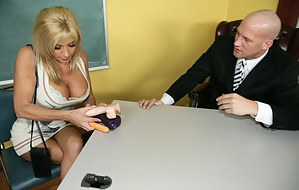 Busty blonde MILF with an awkward hair-metal-like hairdo is busy seducing her underlings, ends up getting fucked in the classroom.