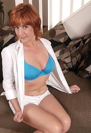 Redheaded MILF Calliste prepares to use a glass dildo on herself