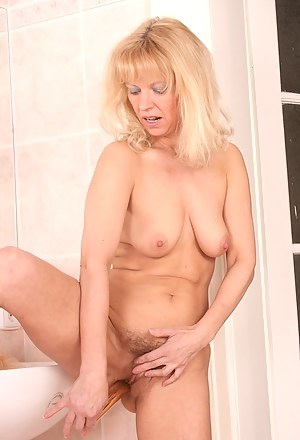 Furry pussied MILF gets it on with a shiny gold vibrator