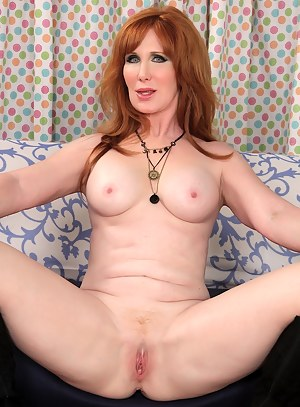 Redheaded granny gets naked and shows her tits and open her legs wide