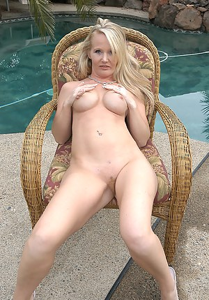 Mature bombshell posing naked out by the pool in this one