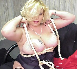 Mature blonde with short hair shows off her big tits while fooling around with some hard ropes, trying to tie herself up with them.