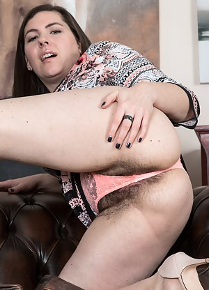 In a colorful dress, Sharlyn strips naked on her leather couch. She completely undresses and sits across her couch. She has such a sexy hairy bush and body, as it spreads across her leather couch.