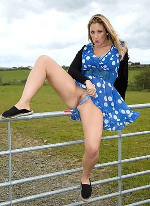 Watch busty MILF Janny Badeau strip and spread in the farmers field