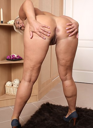 Elegant and busty Melyssa spreading her meaty mature legs here