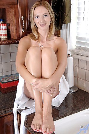 Samantha Rae exposes her natural breasts while spraying her milf pussy in the sink