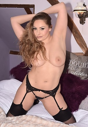 Picture of Sophia Delane on her bed in bra and tiny panties before stripping off to reveal her F cup tits and spreading
