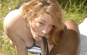Horny red slut sucking on a big black pole