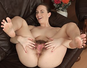 Curvy brunette Erin Eden takes off her see through panties and spreads her hairy ass cheeks with her hands.