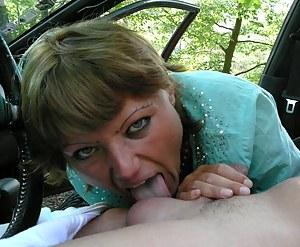 Matue slut sucking two cocks on a parkinglot