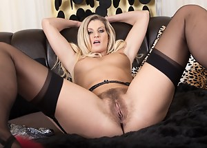 Melania is a sexy blonde beauty wearing black lingerie and stockings as she lays on the couch and slowly strips out of her clothes and uses a beaded dildo on her warm hairy pussy while masturbating.