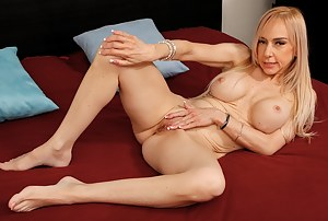 Busty blonde cougar Mirabella Amore pleasures her pussy.