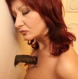 This mature slut sucks black cock through the hole
