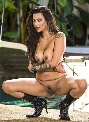 Muscular man is banging the tattooed brunette wearing the short black and purple skirt. He is penetrating her wet ass next to the big pool.