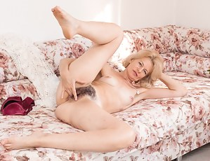Diana Douglas is watering her plants when the feeling of masturbating hits her. She strips naked on her sofa and enjoys her naked hairy body. She touches her pussy all over and has hot times.