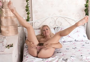 Elle MacQueen poses in bed in her pink lingerie. Her hairy pussy peeks out of the panties and she strips naked afterwards. She spreads her 5'5 blonde and sexy body across her bed perfectly.