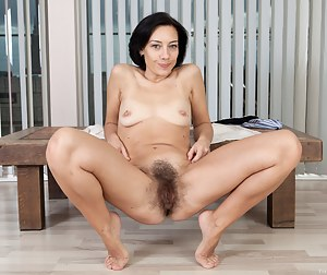 Eva has one of the hairiest pussies ever. Pealing off her top to reveal her small tits, she works her panties down to let out her hairy bush. Spreading her legs wide Eva shows off her lips and muff.